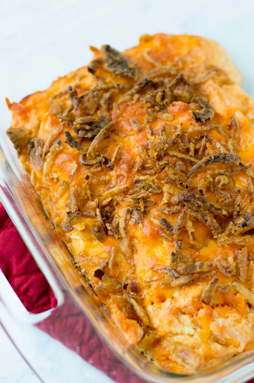 Where I come from, holidays often involve squash casserole, as it is a Deep South Dish. It is a keto friendly comfort food that can be prepped ahead of time. Sliced squash or zucchini is baked in a cheesy cream sauce and topped with extra onions and parmesan cheese. This low carb and gluten free casserole will be a family favorite at your next gathering #yellowsquash #squashcasserole #ketorecipe #lowcarb #zucchini